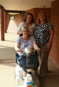 Gail Dungey, the hostel superintendent of Golden Hours School, receiving an electronic scooter from Rotarians Vanessa Champion and Alma Maxwell